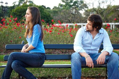 strangers: Man and woman sitting on opposite sides of park bench Stock Photo
