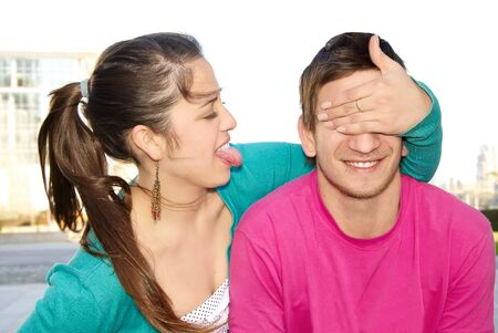 hands covering eyes: Portrait of a happy woman covering his boyfriends eyes to surprise him