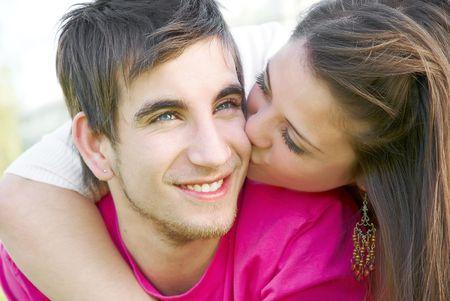 Jonge gelukkige aantrekkelijke paar kussen buitenshuis