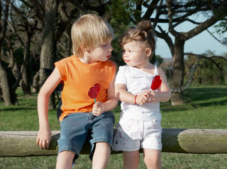 boy and girl sitting on the beam in the park with caramel Stock Photo