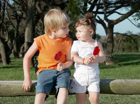 jongen en meisje, zittend op de boom in het park met karamel  Stockfoto