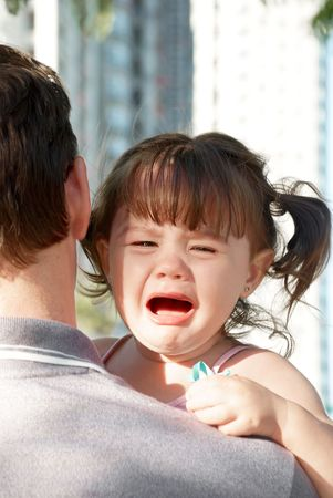young girl crying on her fathers shoulder Stock Photo