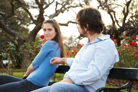 the sides: Man and woman sitting on opposite sides of park bench Stock Photo