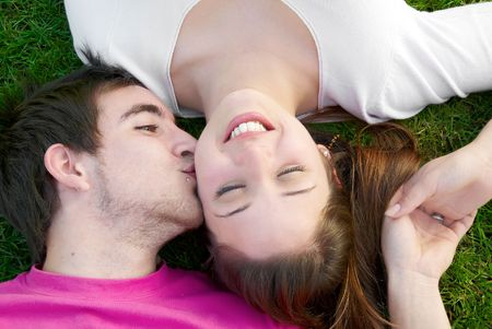 Young love couple kissing on the green grass Stock Photo