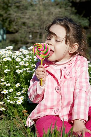 little girl licking lollipop candy in the park Stock Photo - 7904275