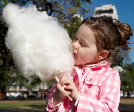 cotton candy: Cute girl eating candy-floss in the park