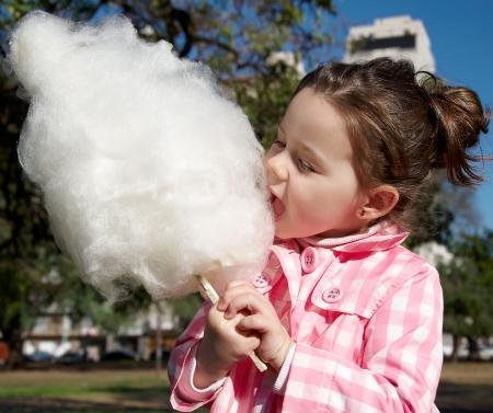 algodon de azucar: Ni�a bonita comer dulces-floss en el Parque  Foto de archivo