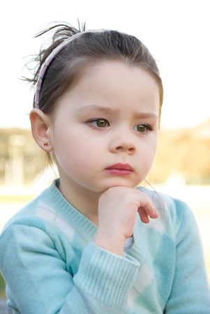 Beautiful little girl thinking in the park photo