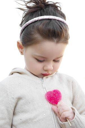 Little girl with the heart shape lollipop photo