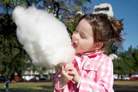 Cute girl candy-floss eten in het park Stockfoto - 8035126