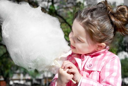 Cute girl eating candy-floss in the park photo