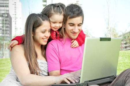 Family of three people plaing in the park with laptop photo