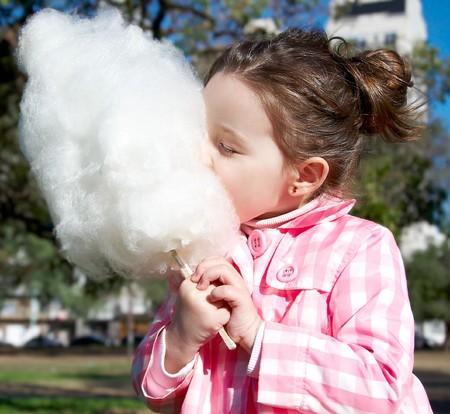Leuk meisje candy-floss eten in het park