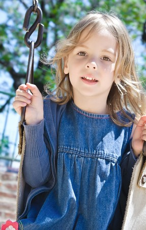 nice little girl on the playground, swinging photo