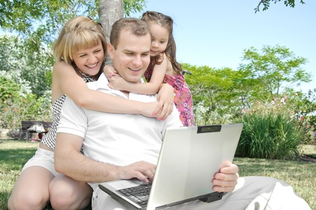 Happy family enjoy laptop outdoors in the park photo