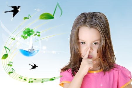 A primary aged girl with her finger on her lips making a shush or shh gesture. photo