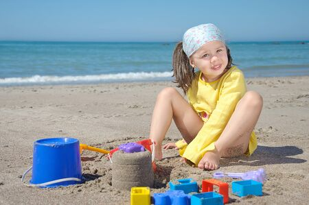 Child playing on the beach and building sand castle photo