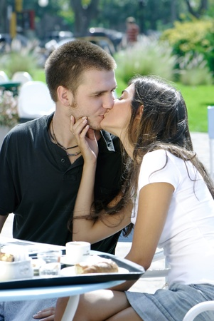 loving couple kissing in a coffee bar outside