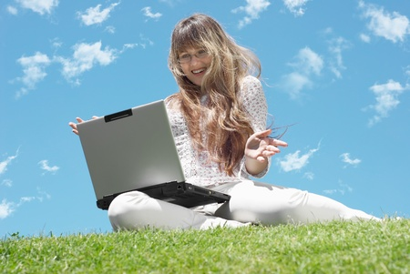 Portrait shot of a beautiful woman in a park with laptop photo