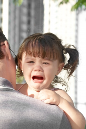 young girl crying on her father photo