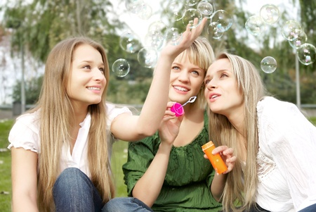 three girls inflating soap-bubbles in the park photo