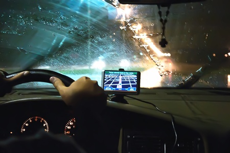 Inside a car night. On the windscreen there is a GPS module.