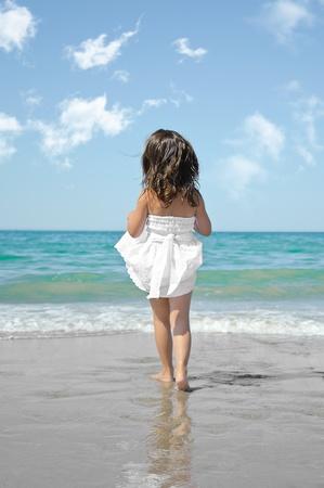 Little girl running beach shore splashing water in blue sea photo