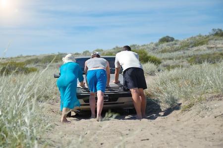 Weinig mensen duwen van een auto die vast in het zand, terwijl safari woestijn