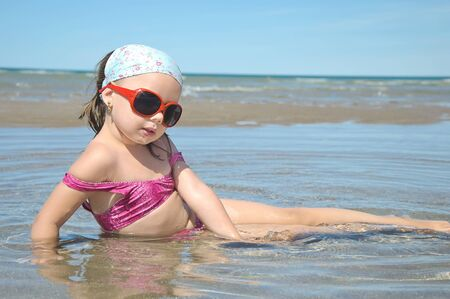 wet suit: The beautiful girl lies on seacoast with sungasses Stock Photo
