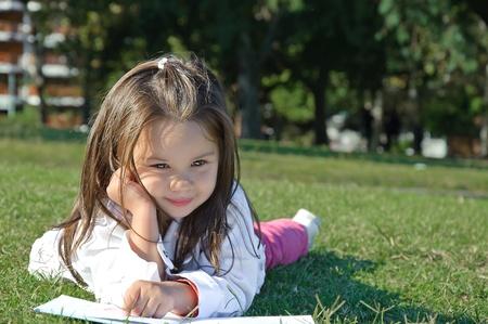 klein meisje tot in het gras en het lezen van