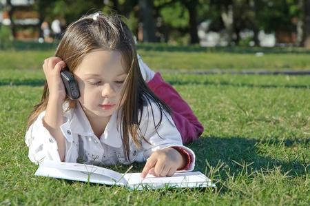 meisje buiten met mobiele telefoon op tha gras