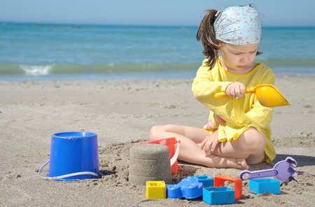 Adorable toddler girl playing with toys on sand beach photo