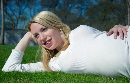Beautiful pregnant woman relaxing on grass photo