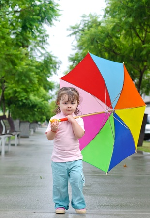 back ground: Adorable toddler girl with colorful umbrella outdoors at autumn rainy day