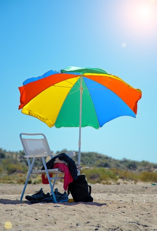 beach chair and colorful umbrella on perfect tropical beach photo