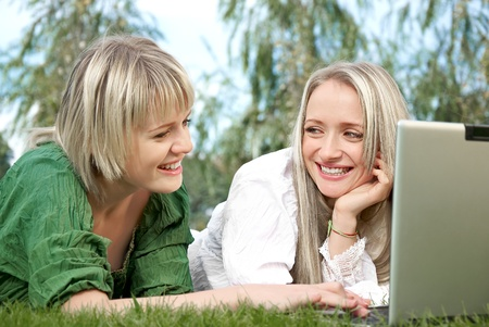 Two Young Woman With Laptop PC at Park photo