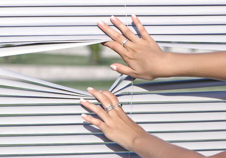 a women hands apart the window blinds photo