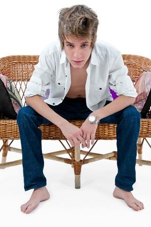 hombres gays: apuesto hombre sentado en un sof� de paja Foto de archivo