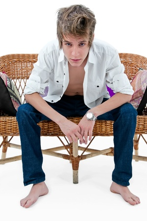 metrosexual: handsome man sitting on a straw sofa