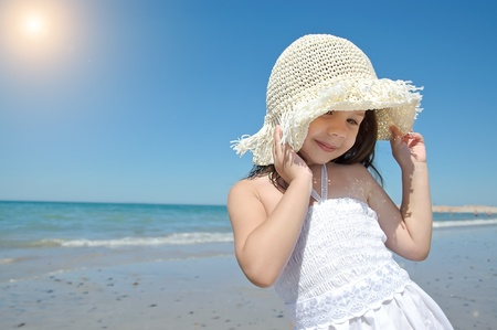 Little girl on the beach wearing funny hat.
