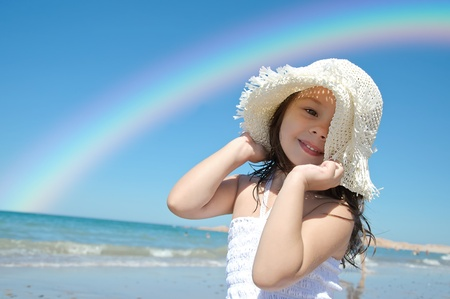 Little girl on the beach wearing funny hat. photo