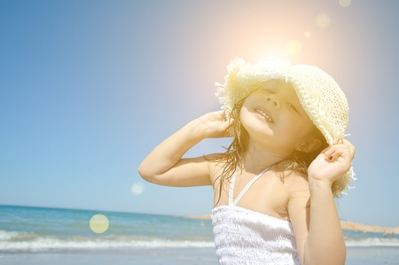 fun in the sun: Little girl on the beach wearing funny hat.