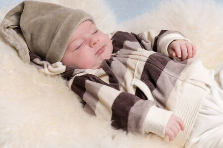 Adorable sleeping baby dressed with a hat photo