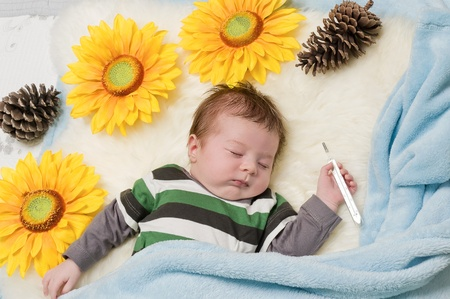 sleeping baby with the thermometer in hand