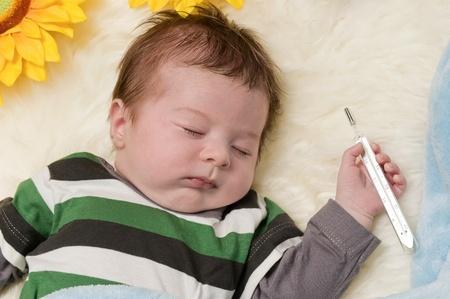 fieber: schlafendes Baby mit dem Thermometer in der Hand