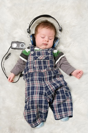 De pasgeboren jongen luisteren naar muziek via oor-telefoons Stockfoto