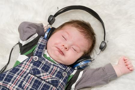 The newborn kid listening to music through ear-phones photo