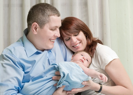 Couple with new born baby at home photo