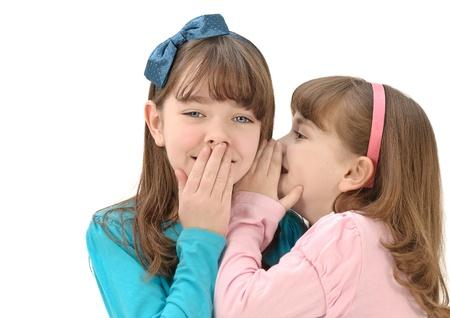 little girls telling secrets isolated on white background Stock Photo