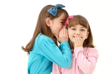 kleine meisjes vertellen van geheimen op een witte achtergrond Stockfoto